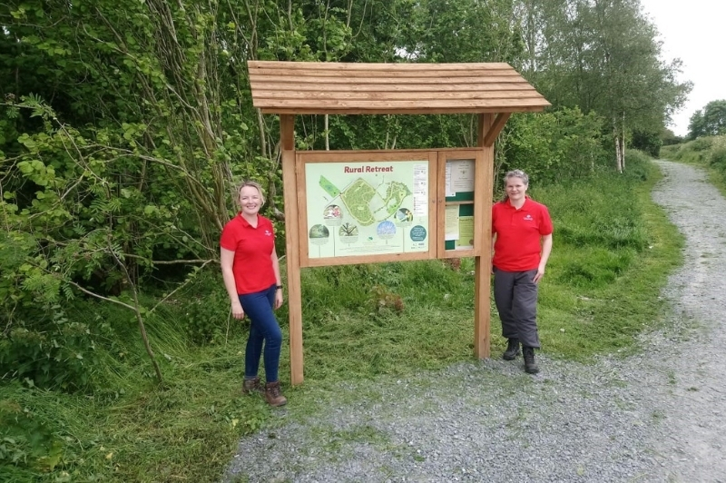 Two staff members stand either side of a map at Glasswater Community Trail.