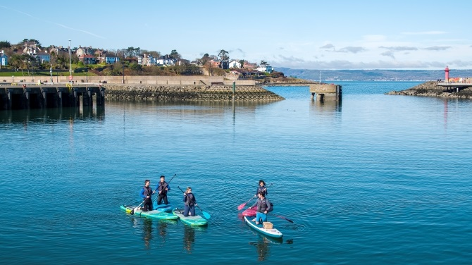 Children playing on paddleboards in a harbour.